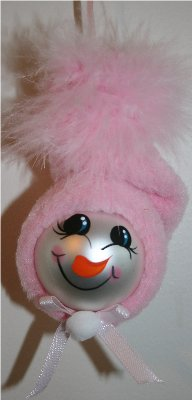 Handpainted Snow Baby Ornament with Pink Fleece Hat and Pink Mirbeau Feathers atop her hat