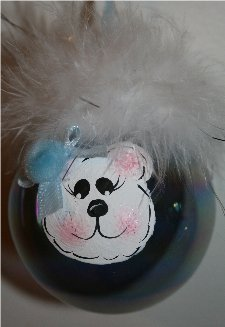 Handpainted Bear Christmas Ornament on a Blue Irredescent Christmas Ornament Accented with Mirbeau feathers and a coordinating ribbon