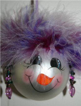 Snowman ornament with purple varigated mirbeau feathers atop her head with matching earrings, and has a handpainted face with rosy cheeks