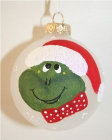 "He's a frog or a grinch, handpainted on a 2 5/8"" frosted ornament.  He has a red hat with a matching red bow tie."