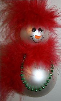 Snowman Ornament created from two glass Christmas balls, trimmed with red mirbeau feathers for her hair and matching mirbeau feathers around her neck for a scarf, accented with green pearls around her neck