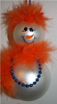 Snowman Ornament created from two glass Christmas balls, trimmed with orange mirbeau feathers for her hair and matching mirbeau feathers around her neck for a scarf, accented with blue pearls around her neck